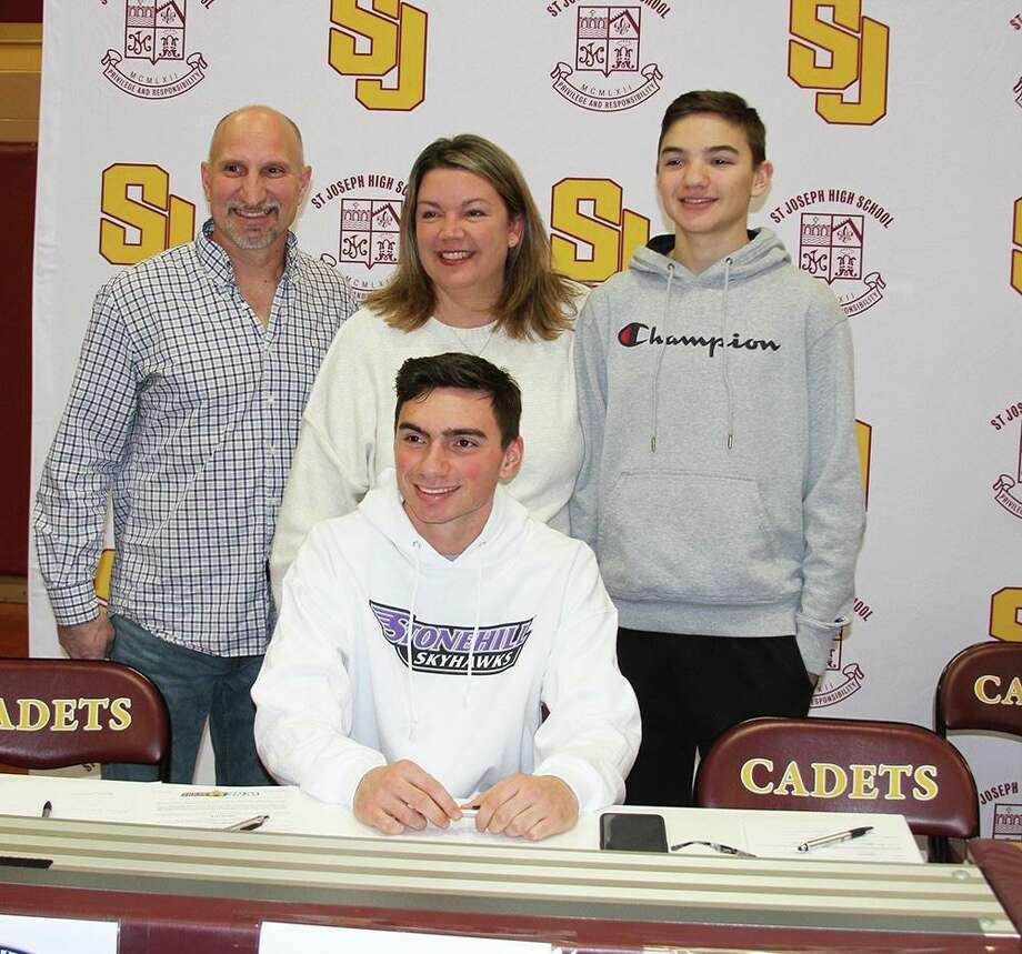 Will Diamantis is joined by dad George, mom Susan and brother Charlie when he signed his letter of intent to play football at Stonehill College in Easton, Mass. Photo: Contributed Photo / St. Joseph Athletics / Trumbull Times