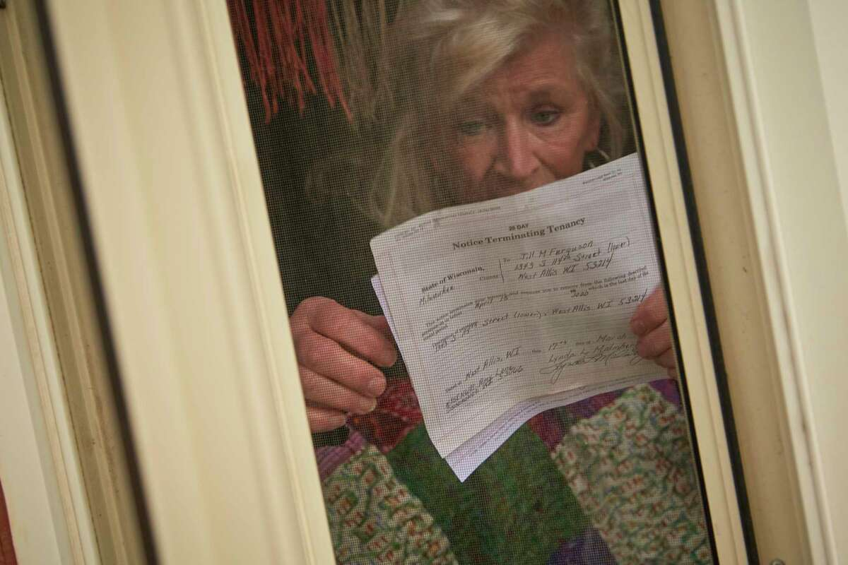 Jill Ferguson, 66 stands for a portrait with a eviction notice at her home last month in West Allis Wis.
