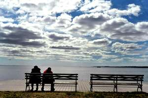 Two people sit closely together as they look from Fort Hale Park in New Haven out onto New Haven Harbor and Long Island Sound during the Covid-19 / Coronavirus pandemic. Many people are practicing social distancing.