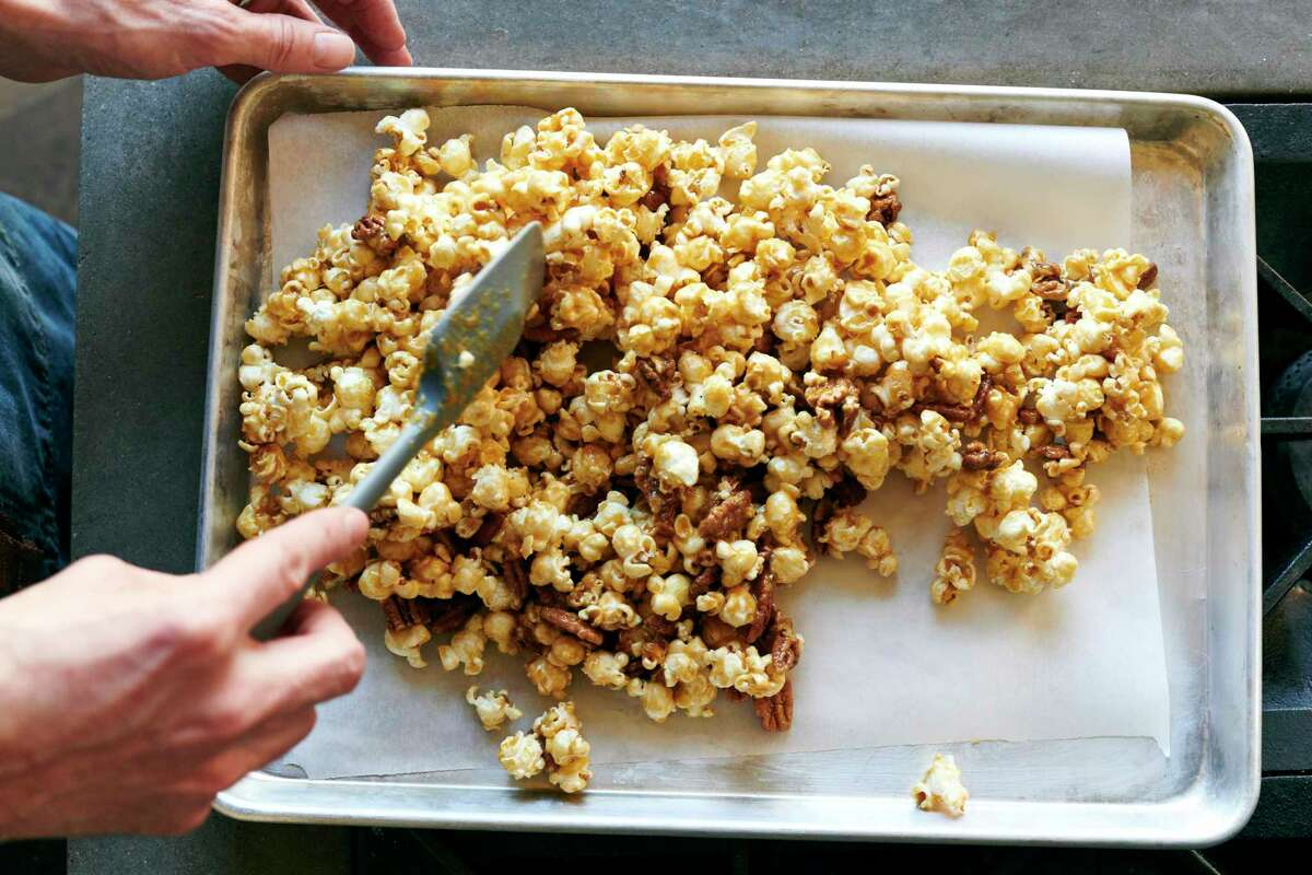 For a caramel corn with a candy-like crunch, use a bit of baking soda. Once coated, the popcorn goes into the oven for about half an hour. (David Malosh/The New York Times)