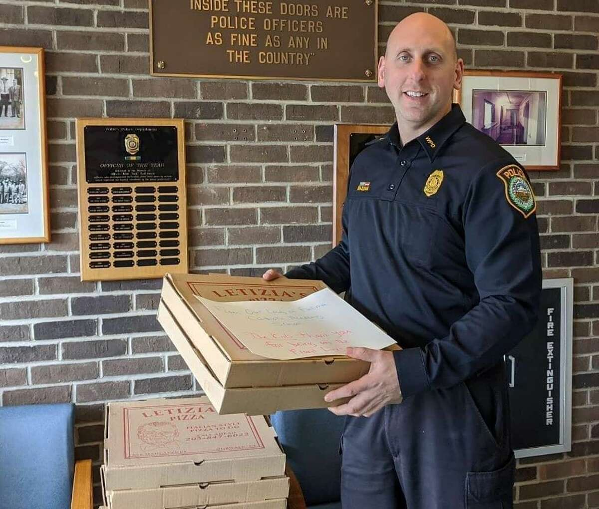 Wilton Police Officer Frank Razzaia accepts a delivery of pizzas on behalf of the department courtesy of students and families of Our Lady of Fatima Catholic Academy in Wilton, Conn. March 2020
