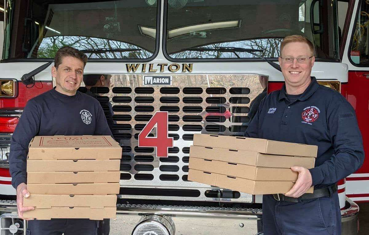Deputy Fire Marshal Kevin Plank and Capt. Brian Elliott accept a delivery of pizzas on behalf of the Wilton Fire Department courtesy of students and families of Our Lady of Fatima Catholic Academy in Wilton, Conn. March 2020