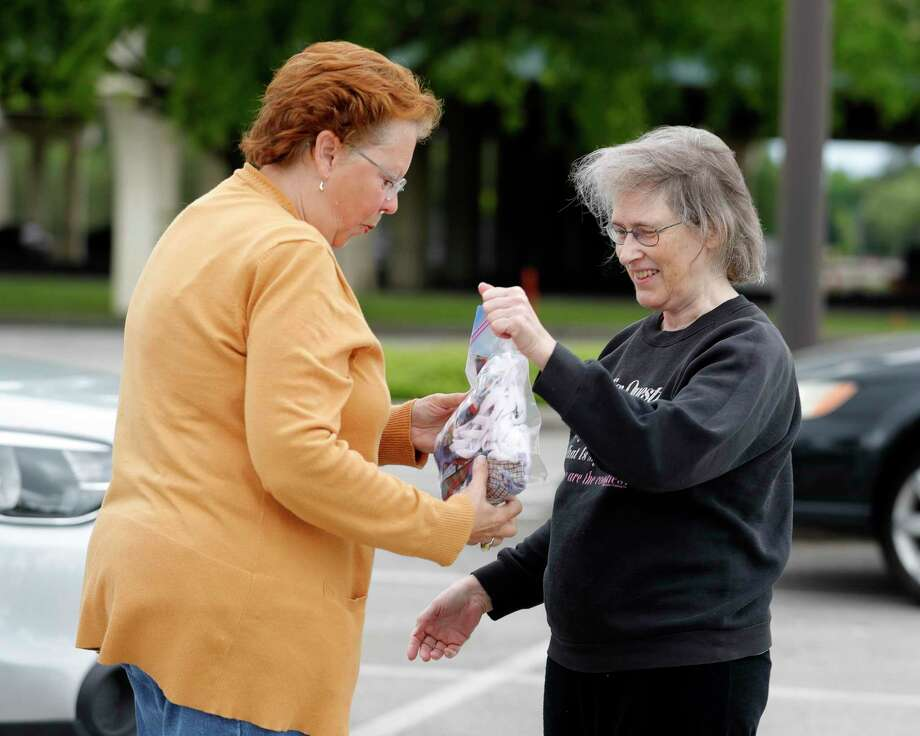 Jane Carver, president of the Golden Needles Quilt Guild, takes a bag full of hand-made masks from Diane Miller, Tuesday, March 31, 2020, in Conroe. The organization collected more than 200 hand-made masks from its members to be given to Tri-County Service for its medical workers Photo: Jason Fochtman,  Houston Chronicle / Staff Photographer / 2020 © Houston Chronicle