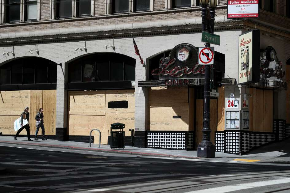 Pedestrians walk by a boarded up restaurant on March 31, 2020 in San Francisco, California. Officials in seven San Francisco Bay Area counties announced on Monday plans to extend the shelter in place order until May 1 due to coronavirus concerns.