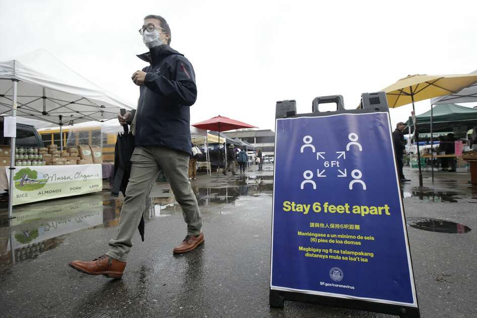 A man walks past a sign advistng social distance at the Ferry Plaza Farmers Market in San Francisco, Saturday, March 28, 2020. (AP Photo/Jeff Chiu)
