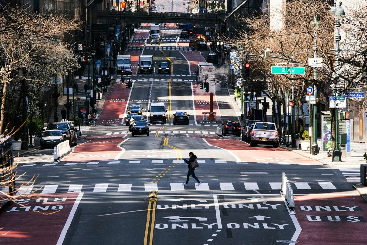 NEW YORK, NY - MARCH 26: A woman crosses 42nd Street as it is seen with low traffic due to the coronavirus outbreak on March 26, 2020 in New York City. Across the country schools, businesses and places of work have either been shut down or are restricting hours of operation as health officials try to slow the spread of COVID-19. (Photo by Eduardo Munoz Alvarez/Getty Images)