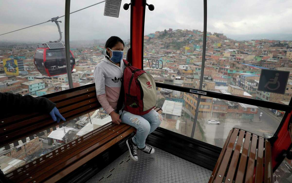 A woman, wearing a protective face mask as a precaution against the new coronavirus, rides in a public cable car in Bogota, Colombia, Wednesday, April 1, 2020. Health authorities have begun checking the temperature of commuters as a measure to contain the spread of COVID-19.