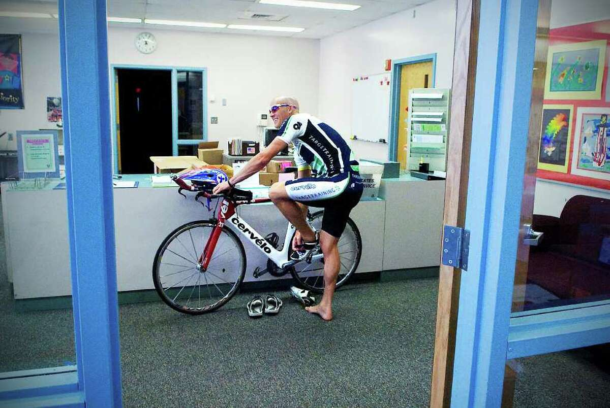 Mitch West, 40, changes out of his biking shoes in the office at Westover Magnet Elementary School in Stamford, Conn. on Thursday August 19, 2010. West, who is a social worker at Westover, competes in Iron Man races, and rides his bicycle to school every day from his home in Wilton.