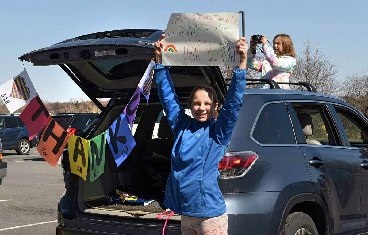 Stella Myers, 12, and her sister Victoria, 9, cheer from their mom's car as staff at New York Oncology Hematology hold signs up to support patients and medical staff inside NYOH's chemo room on Wednesday, April 1, 2020 in Albany, N.Y. While staff outside held signs, members of the Albany Police Department circled around the parking lot with their lights and sirens on. (Lori Van Buren/Times Union)