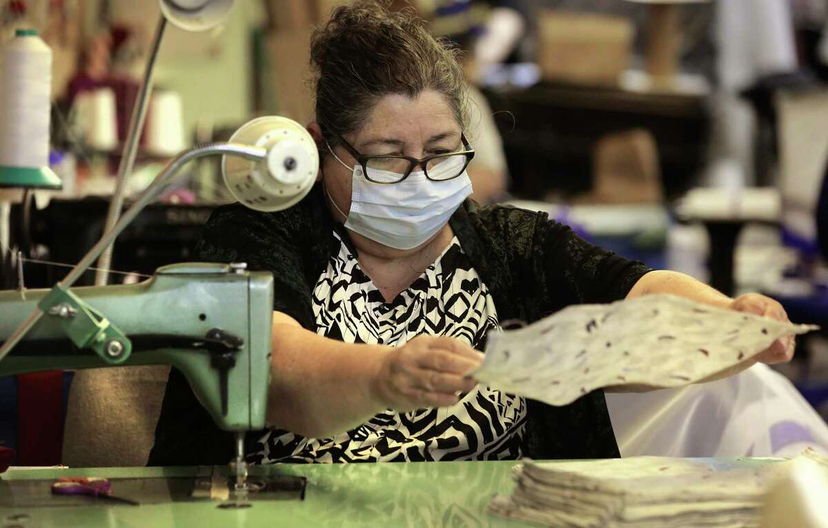 Araceli Rodrigues places an inprocess surgical mask in a stack. Vanessa Van de Putte President of Dixie Flag & Banner Company, has switched some it's production line to surgical masks which are in high demand now, to save some of the worker's jobs, on Tuesday, March 31, 2020.