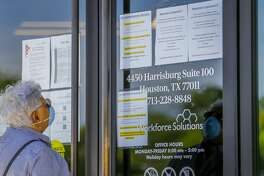 A woman looks at the signs saying that the Workforce Solutions office is closed due to the Covid-19 outbreak, Wednesday, April 1, 2020, on Harrisburg in east Houston. Services are still available online and by phone, but the physical office is closed.