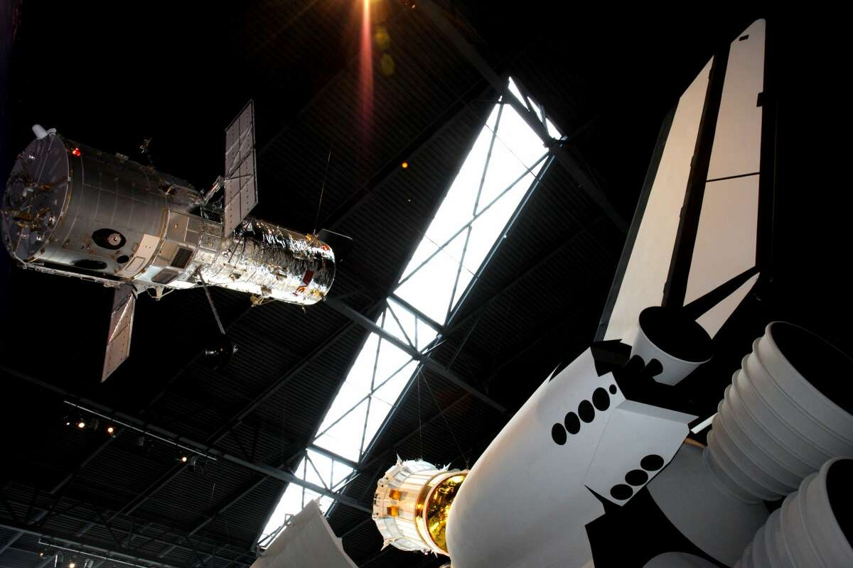 A half-scale model of the Hubble Space Telescope and Boeing Inertial Upper Stage rocket booster are seen floating above the Space Shuttle Trainer at The Museum of Flight in Seattle, Wash.