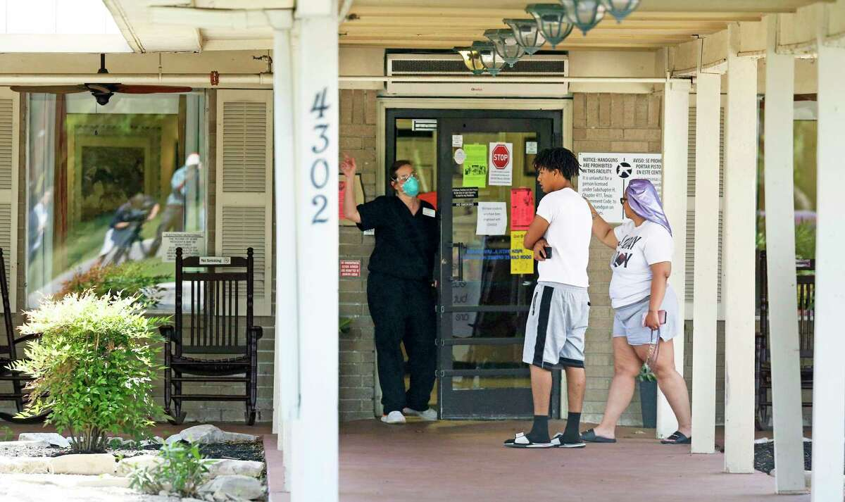 Facility personnel direct a visiting couple to the side of the Southeast Nursing and Rehabilitation Center, where their relative has a room with a window on April 1, 2020. An outbreak of coronavirus was reported there, killing one resident.