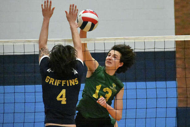 Metro-East Lutheran senior Calvin Cunningham slams down a kill during a match last season at the Belleville East Tournament.