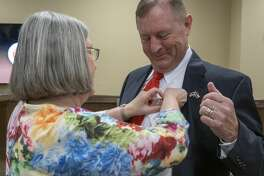 Judy Criner pins on the new Sheriff badge 04/01/2020 after David Criner was sworn in as the new Midland County Sheriff. Tim Fischer/Reporter-Telegram