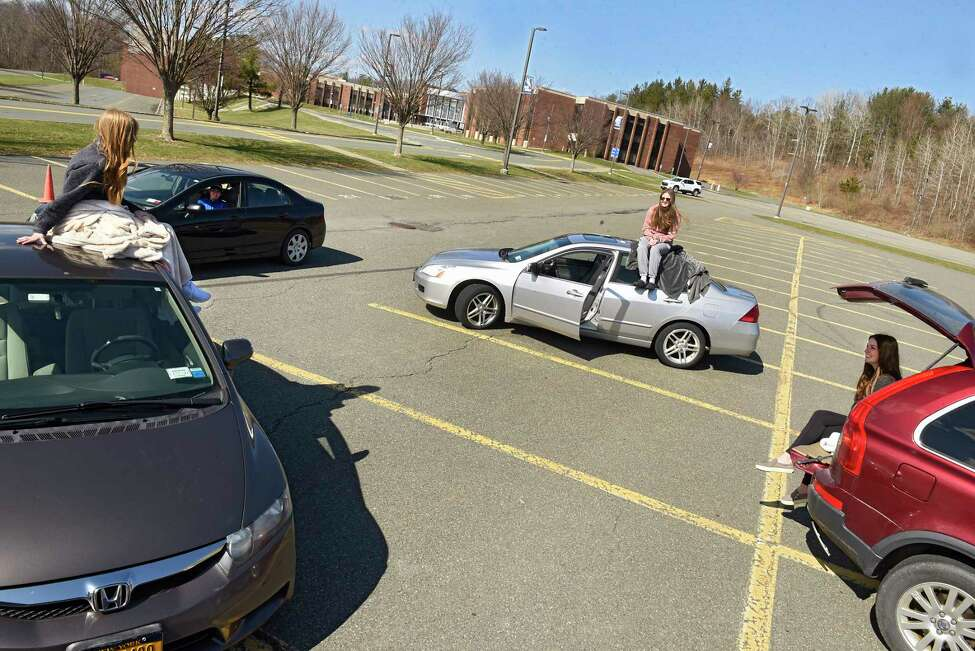 Columbia High School seniors, from left, Julia Poitras, 18, Brady Hoffman, 18, Jessica Vorst, 17, and Ella Conway practice social distancing as they meet up in the school's parking lot on Wednesday, April 1, 2020 in East Greenbush.The Capital Region is bracing for the unknown as local authorities, schools and businesses take measures to prevent the spread of the novel coronavirus.
