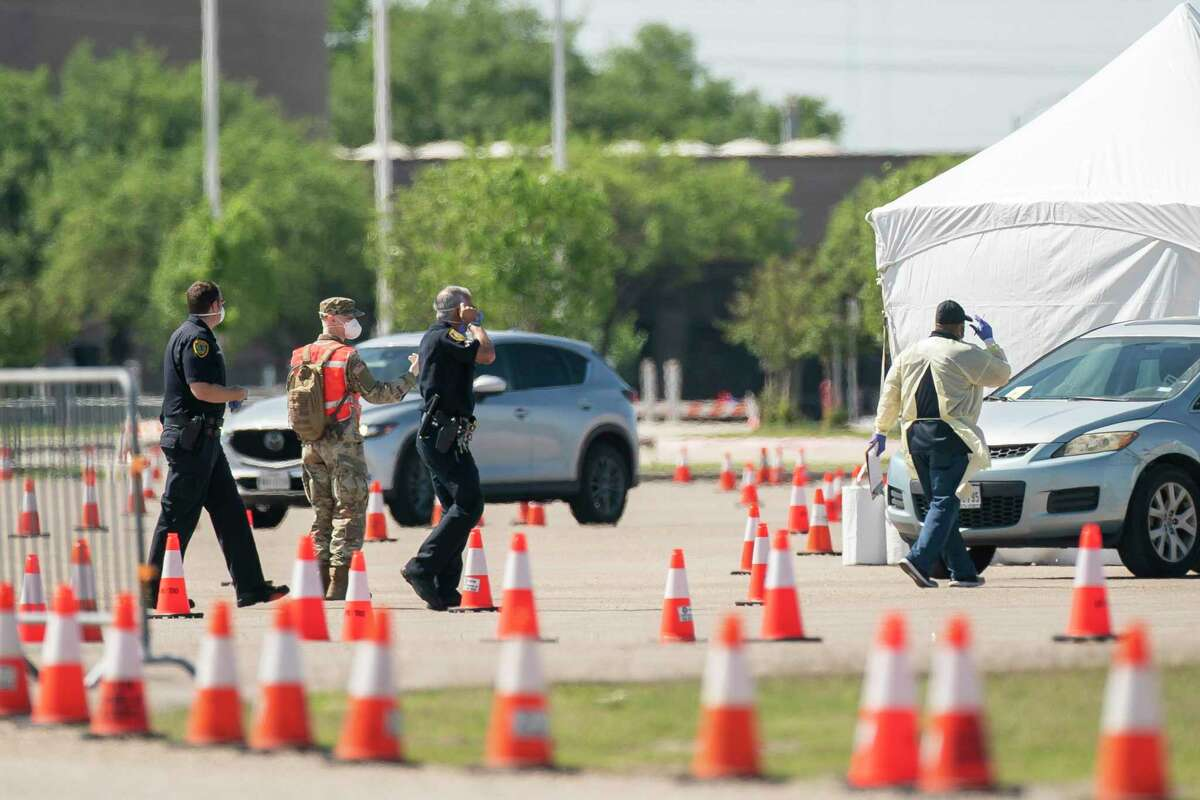 Houston police officers, medical professionals and members of the National Guard work together to help move people through the line at the city's newest COVID-19 testing site, Wednesday, April 1, 2020, at Delmar Stadium in Houston. People who come to the site must have been pre-screened and brought a unique identification number given to them during the pre-screening to access the testing site.