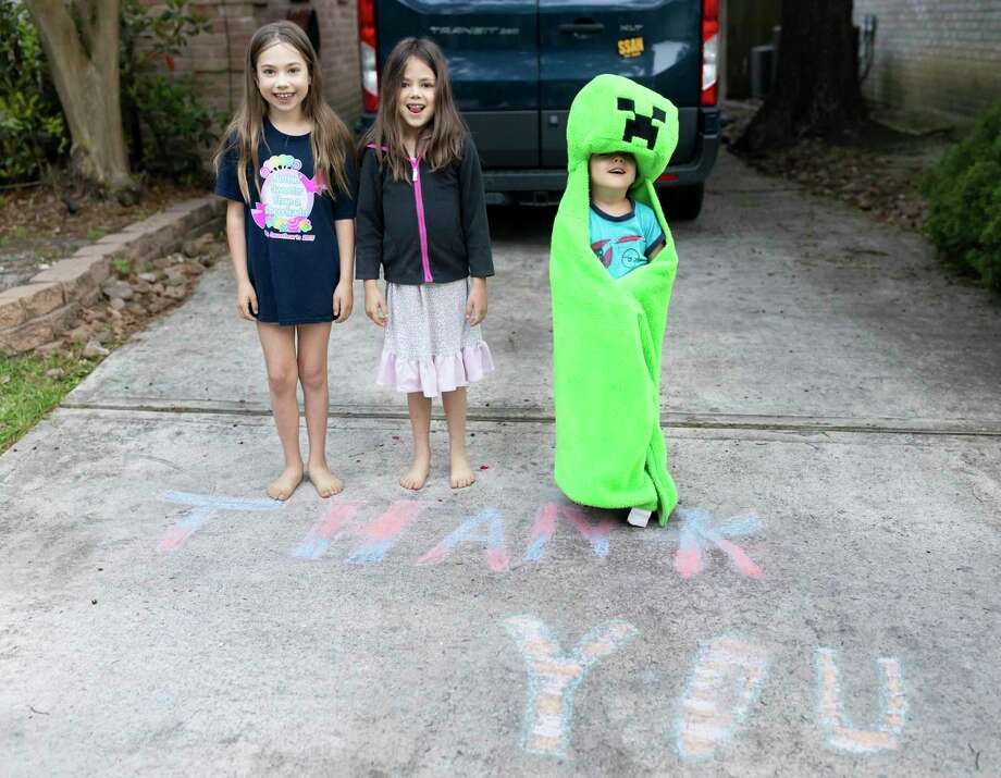 From left to right, Chloe, Danae and Eland Lorenz pose behind chalk art thanking Residential Recycling & Refuse of Texas employees, Monday, March 30, 2020. Photo: Gustavo Huerta, Houston Chronicle / Staff Photographer / Houston Chronicle © 2020