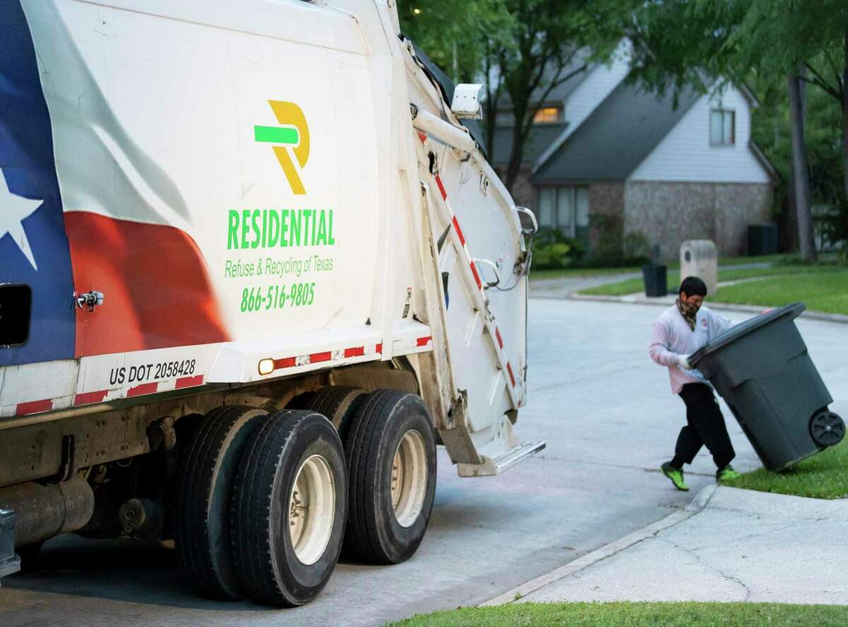 A Residential Recycling & Refuse of Texas employee takes a garbage can off the curb, Monday, March 30, 2020.