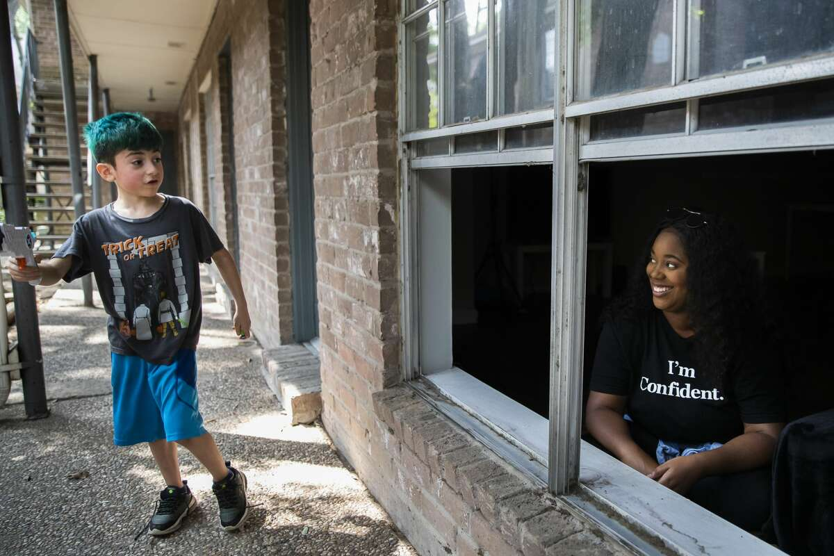 Chantel Smith, 26, talks to her neighbor from her apartment on Monday, March 30, 2020, in Houston.