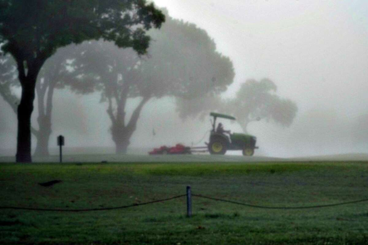 A groundskeeper is seen through the dense fog as he maintains the greens and fairways at Olmos Basin Golf Course on March 25. This week, the course was closed pending results of a COVID-19 test of an ill employee who cleans golf carts there.