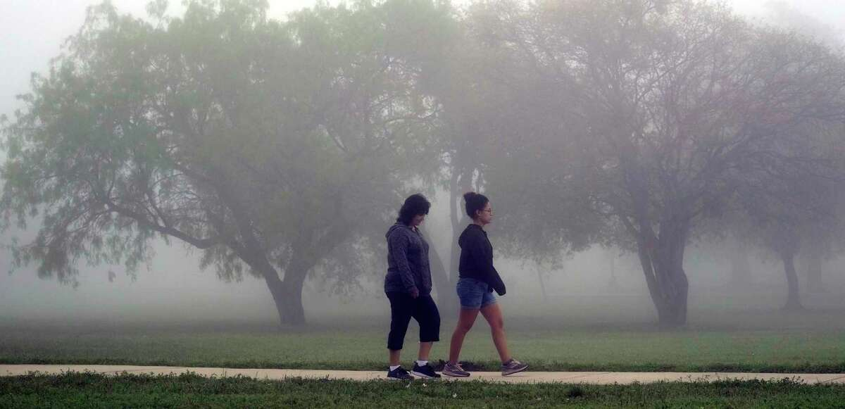 Dozens of joggers and walkers are seen thorugh the dense fog as they exercise at Shearer Hills/Ridgeview Walking Trail and Olmos Basin Park on March 25, This week, the nearby golf course was closed pending results of a COVID-19 test of an ill employee who cleans golf carts there.