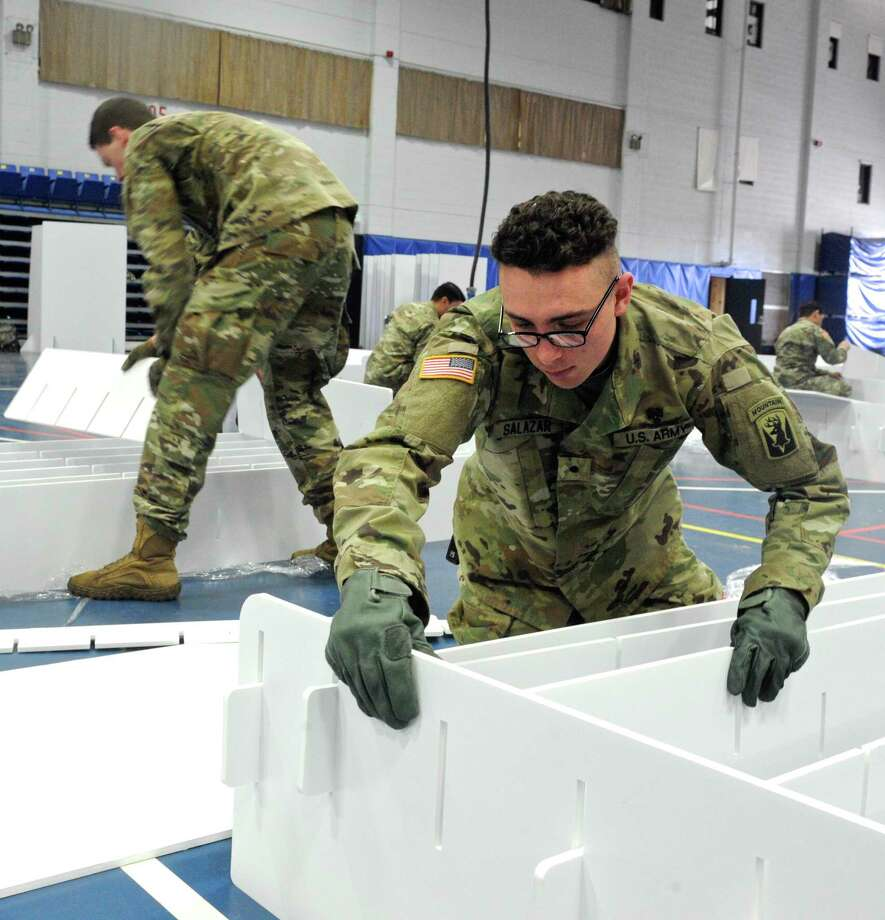 Cadet Andre Salazar, of Bridgeport, assembles a bed as the national guard arrived Wednesday at the O'Neill Center on Western Connecticut State University Westside campus to begin to transform the building into a 219 bed medical space that would be used if area hospitals see a surge in patients. Wednesday, April 1, 2020, in Danbury, Conn. Photo: H John Voorhees III / Hearst Connecticut Media / The News-Times