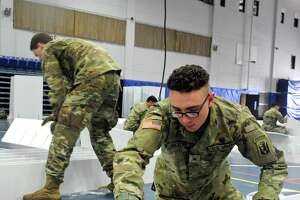 Cadet Andre Salazar, of Bridgeport, assembles a bed as the national guard arrived Wednesday at the O'Neill Center on Western Connecticut State University Westside campus to begin to transform the building into a 219 bed medical space that would be used if area hospitals see a surge in patients. Wednesday, April 1, 2020, in Danbury, Conn.