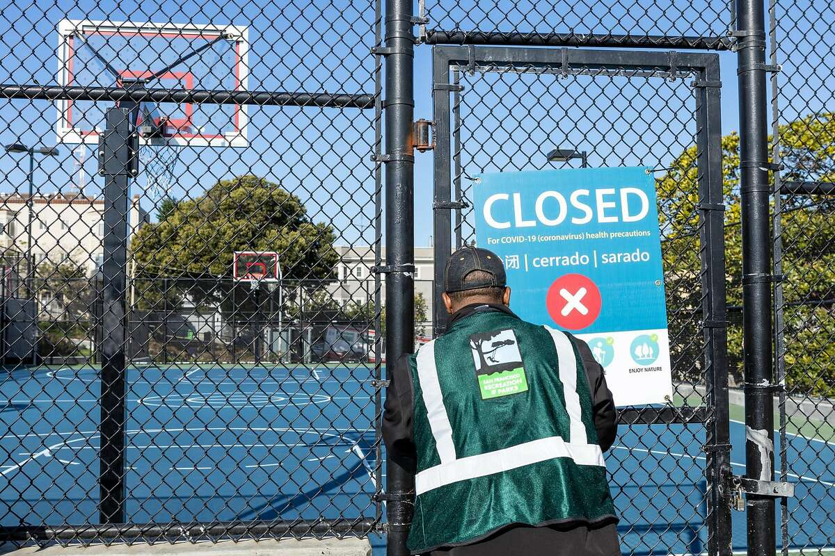 A man (no name given) hangs a closed sign on the gate of the basketball court at Dolores Park on Wednesday, April 1, 2020, in San Francisco, Calif.�