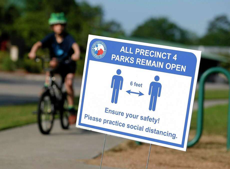 A sign reminds visitors at Dennis Johnston Park to practice social distancing, Thursday, March 27, 2020, in Spring. Photo: Jason Fochtman, Houston Chronicle / Staff Photographer / 2020 © Houston Chronicle