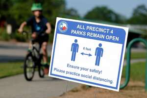 A sign reminds visitors at Dennis Johnston Park to practice social distancing, Thursday, March 27, 2020, in Spring.