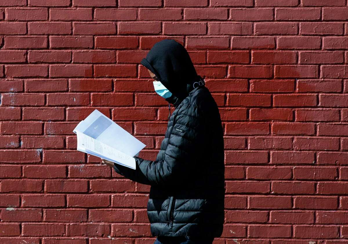 In this Thursday, March 26, 2020, photo, Terrell Bell, wearing a protective face mask, looks at a learning guide he picked up for his little sister at John H. Webster Elementary School in Philadelphia. Only about half of the district's high school students have a laptop or tablet and home internet service. As schools now appear likely to be closed due to the coronavirus outbreak for longer than anticipated, the district plans to buy 50,000 Chromebooks and begin online instruction by mid-April. (AP Photo/Matt Rourke)