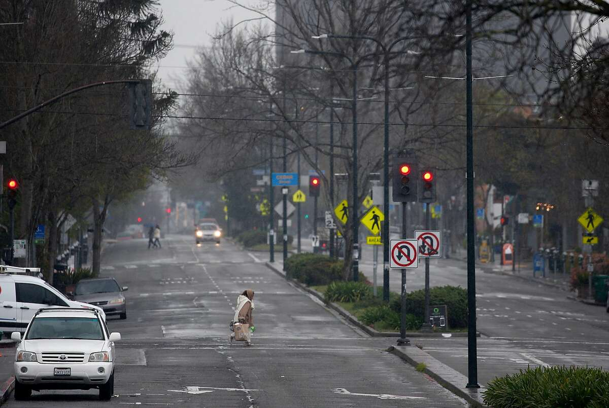A woman crosses Shattuck Avenue which is normally filled with traffic in Berkeley, Calif. on Saturday, March 28, 2020. Air quality has improved significantly as fewer vehicles are on the streets and highways while shelter in place orders remain in effect during the coronavirus pandemic.