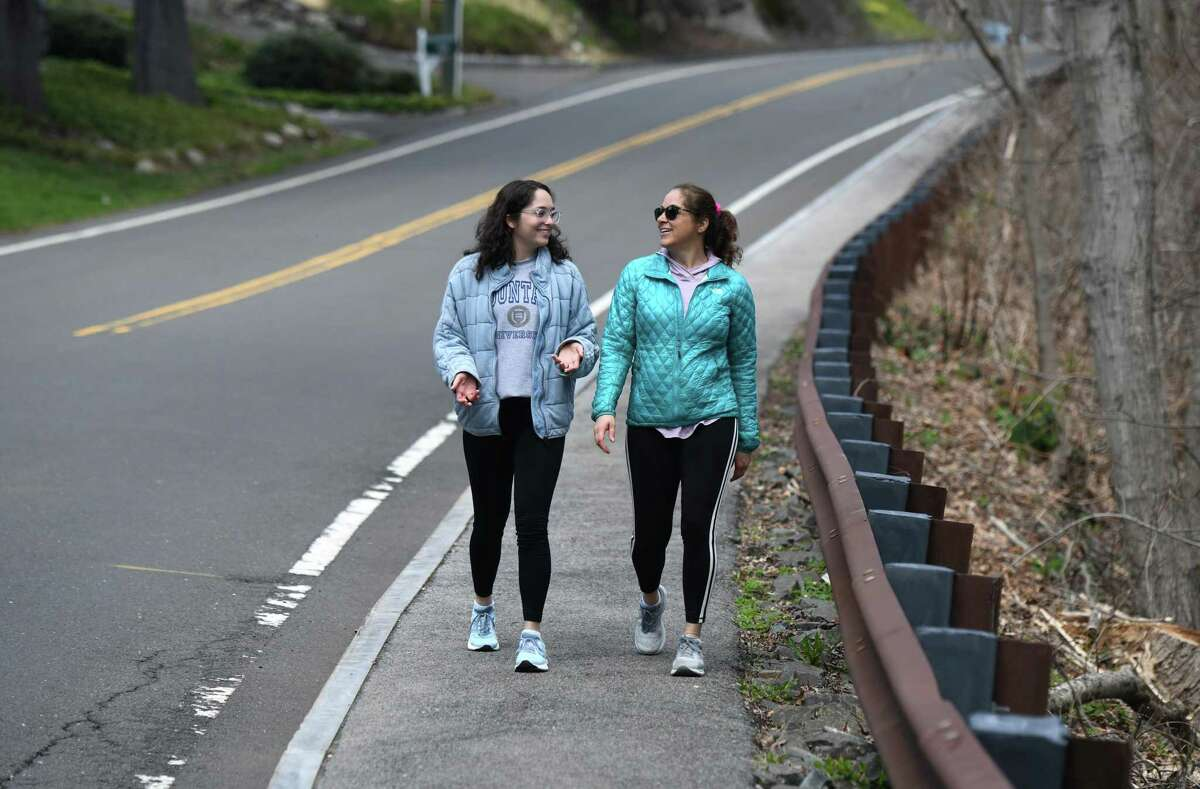 Old Greenwich residents Emily Fountain, left, and Anne Fountain walk on the sidewalk in the Cos Cob section of Greenwich, Conn. Wednesday, April 1, 2020. With Greenwich parks closed, town sidewalks and roads have been seeing a higher volume of foot traffic.