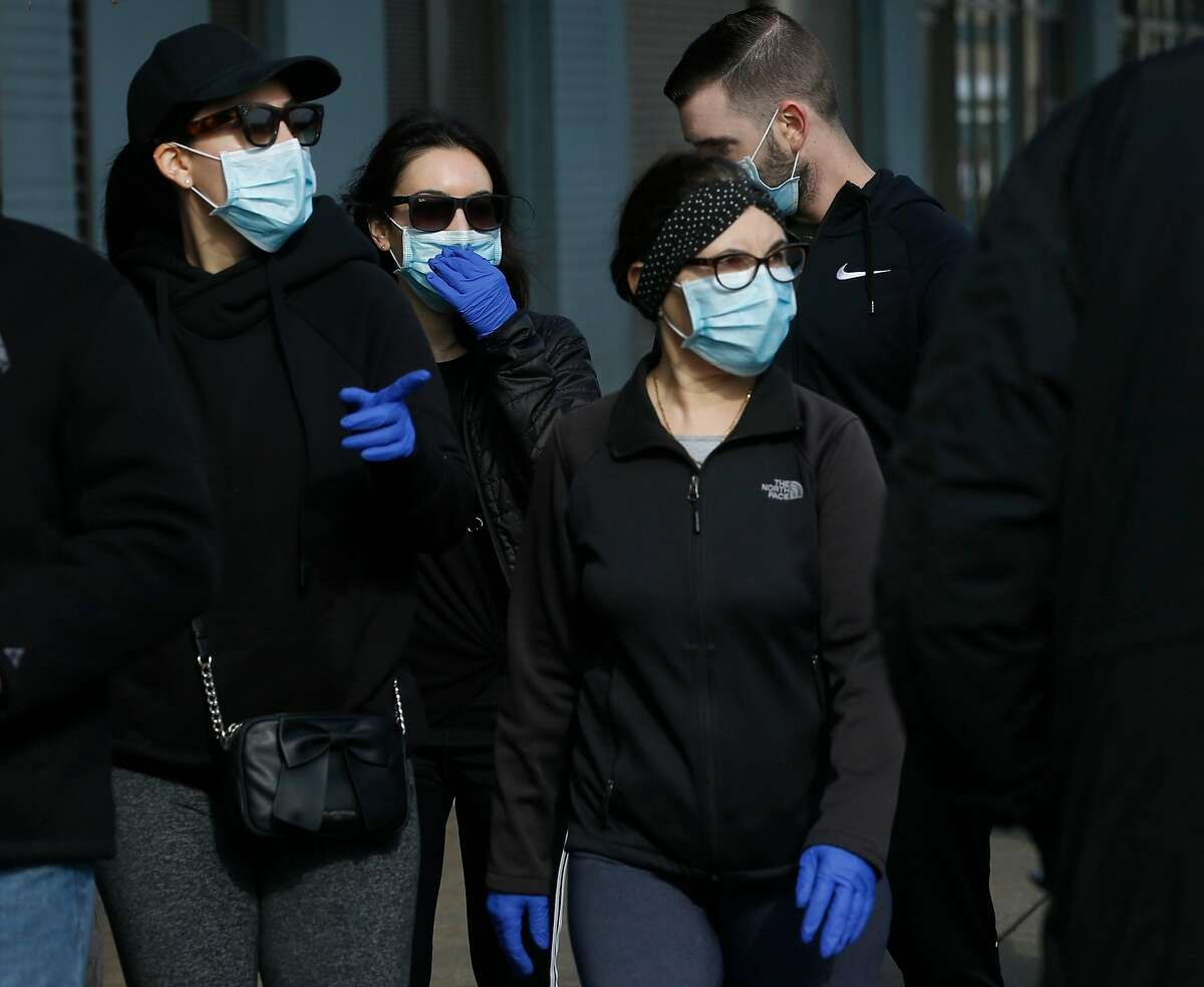 Ferry Plaza Farmers Market customers wear protective masks in San Francisco, Calif. on Saturday, March 21, 2020 as the shelter in place order remains in effect to slow the spread of the coronavirus pandemic.