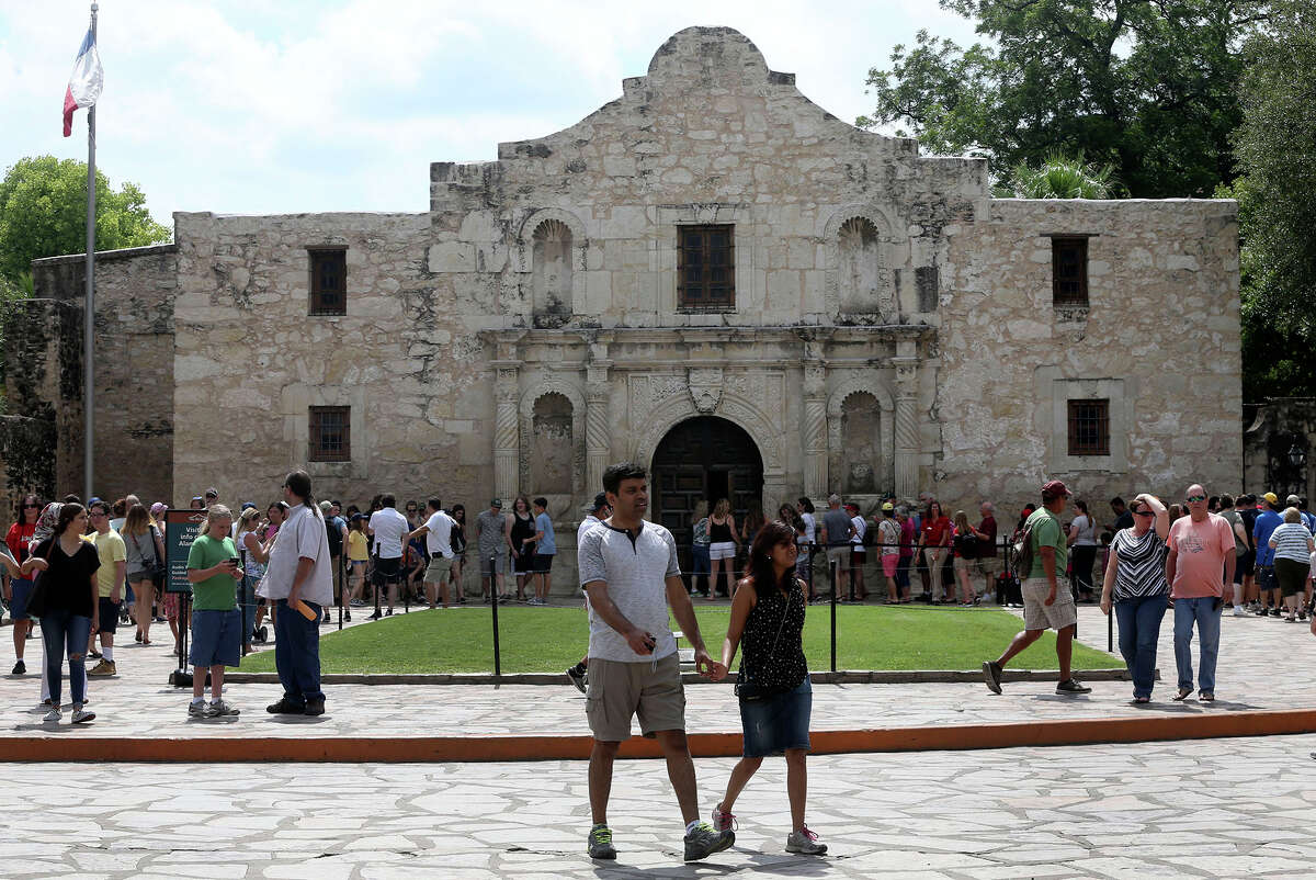 Tourists and visitors walk in front of the Alamo on July 3, 2017.