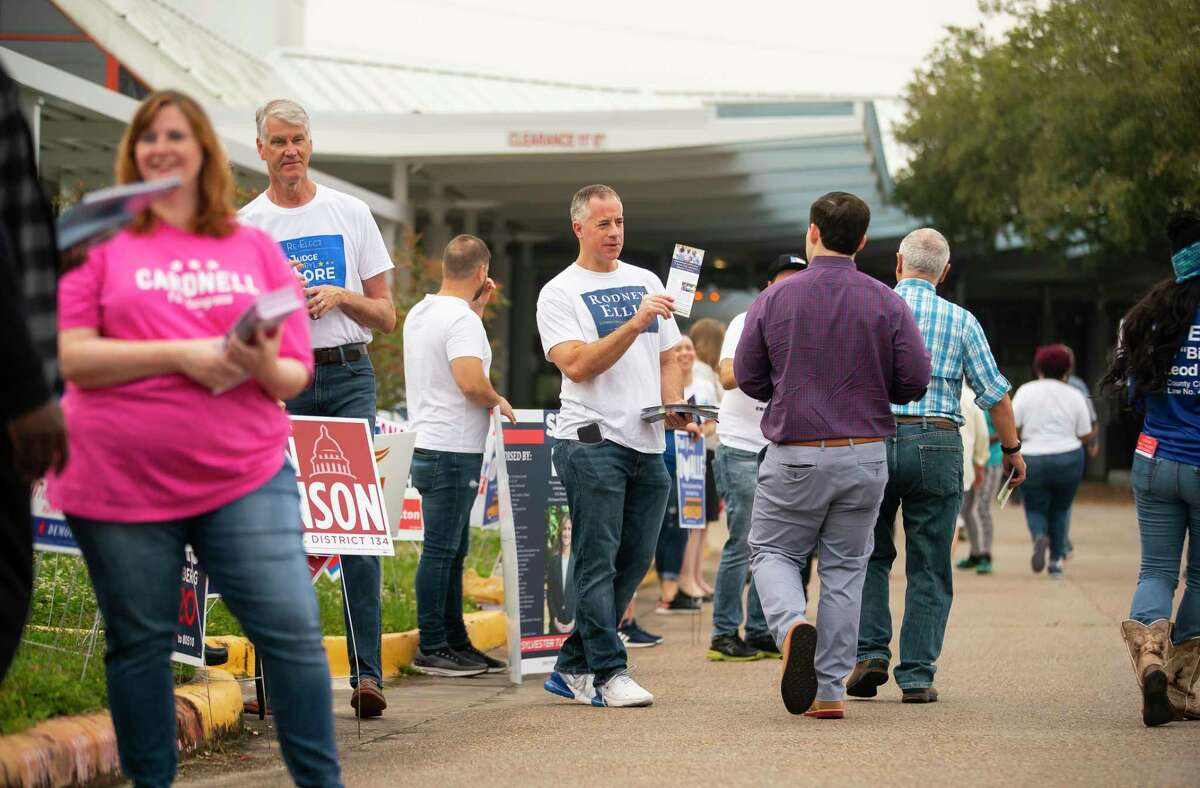 Campaign workers crowd outside a polling place as they greet voters, an unthinkable scene under current social distancing measures to fight the coronavirus.