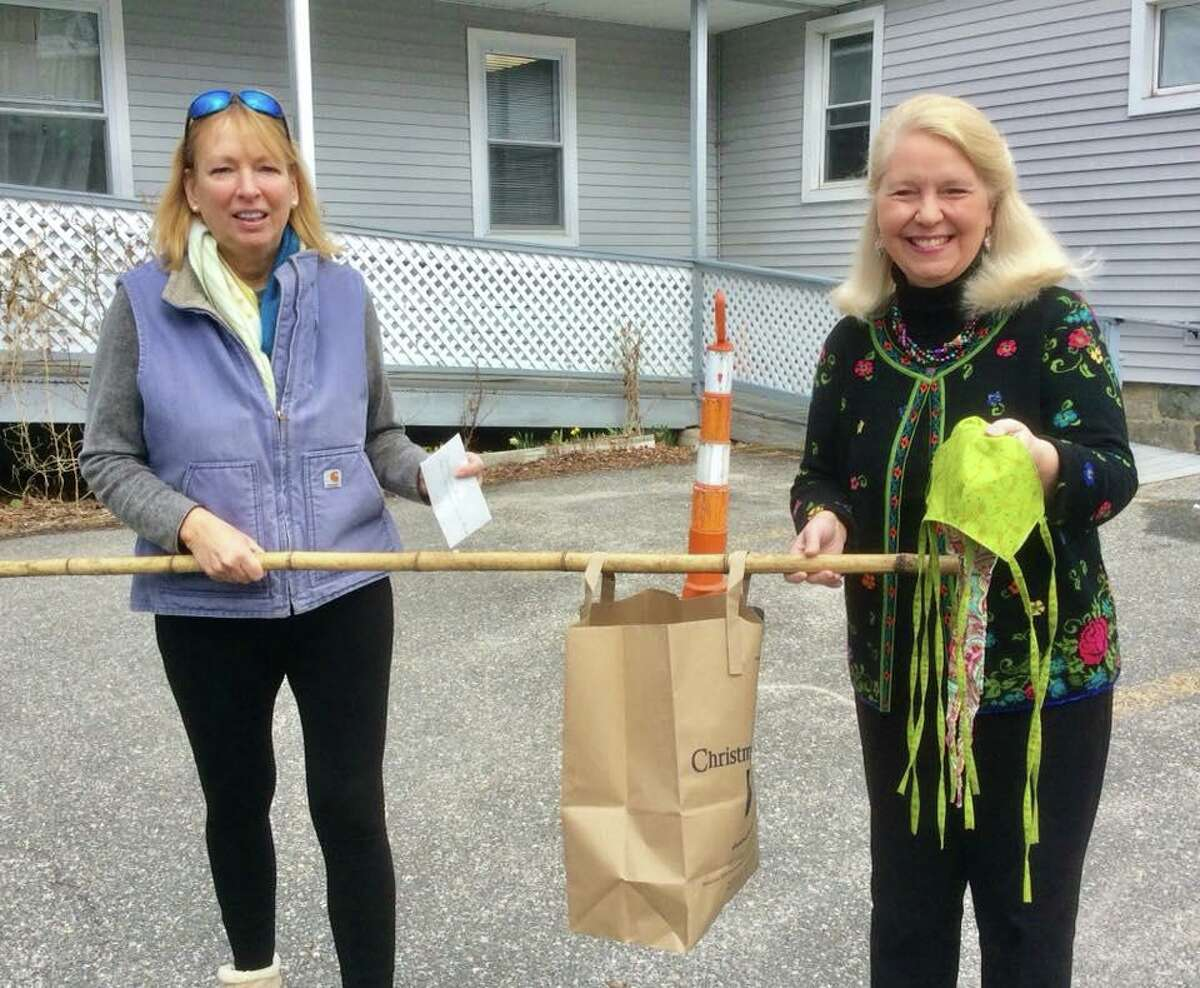 Lori Kibbe Lindenmuth, left, delivered handmade protective masks to Deirdre DiCara, executive director of FISH.