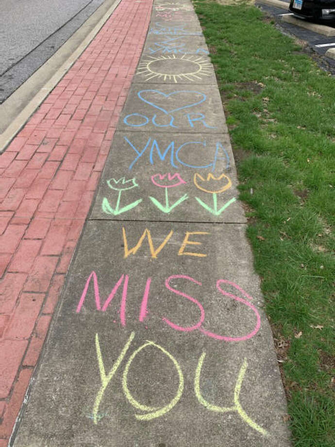The sidewalk in front of the Niebur Center YMCA on Esic Drive is covered with a message from branch manager Monica Snook, who sends regards to members while all Edwardsville YMCA facilities are closed to the coronavirus pandemic. Photo: For The Intelligencer