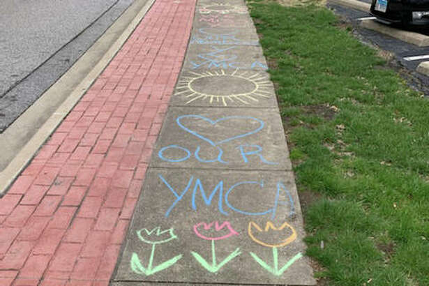 The sidewalk in front of the Niebur Center YMCA on Esic Drive is covered with a message from branch manager Monica Snook, who sends regards to members while all Edwardsville YMCA facilities are closed to the coronavirus pandemic.
