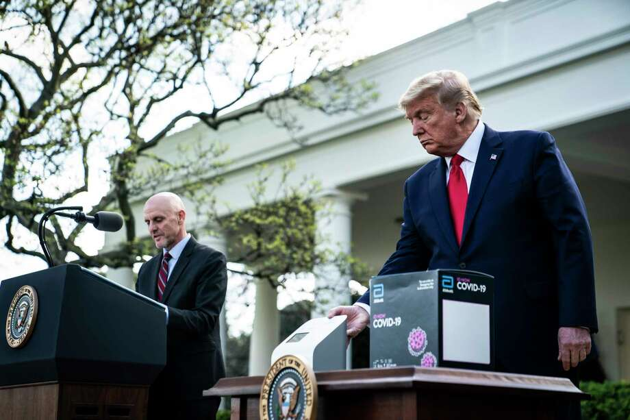 President Donald Trump shows off a new test kit for covid-19 that can produce results in five minutes. Photo: Washington Post Photo By Jabin Botsford / The Washington Post