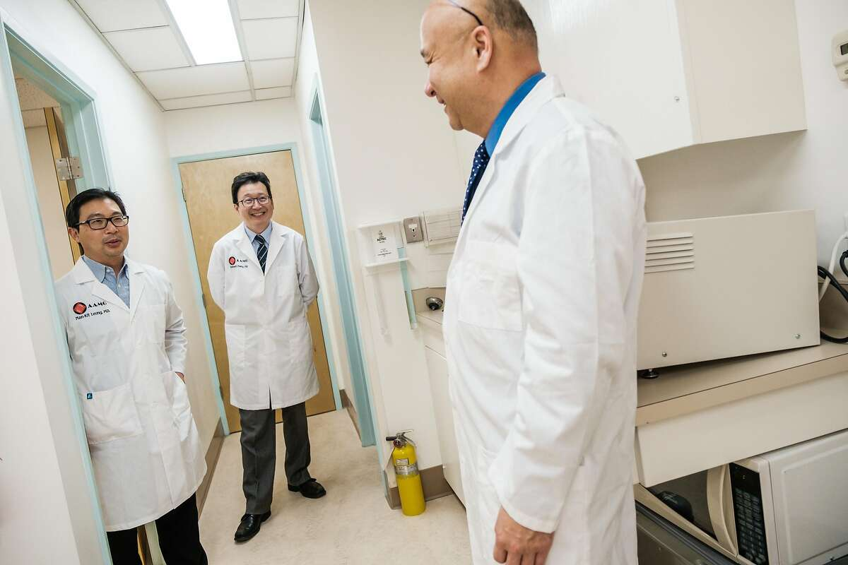 Dr. Man-Kit Leung, left, chats with Dr. Kenneth Chang, back, and Dr. Joseph Woo at Dr. Leung's office in San Francisco, Calif. on Wednesday April 1, 2020.