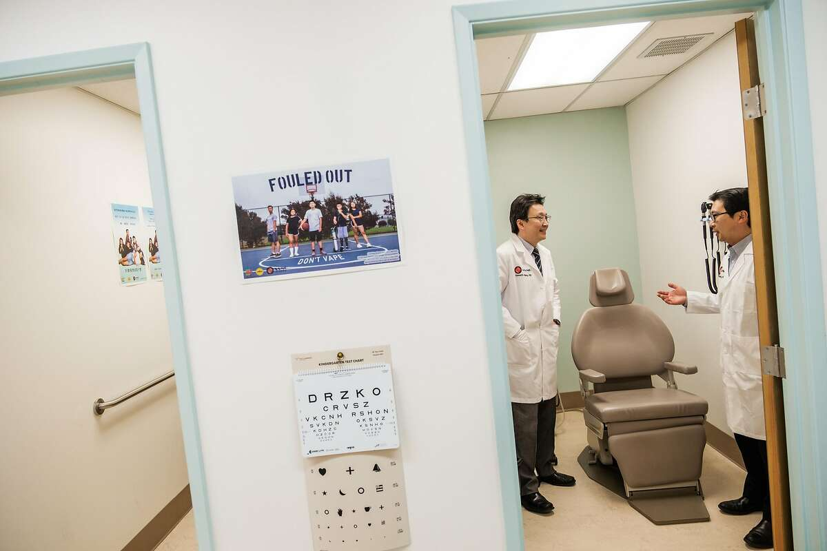 Dr. Kenneth Chang, left, chats with Dr. Man-Kit Leung at Dr. Leung's office in San Francisco, Calif. on Wednesday April 1, 2020.