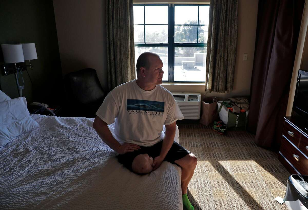 Chad Baker, RN, in his hotel room where he has been living away from his husband in Richmond, Calif., on Tuesday, March 31, 2020. Baker is an ER nurse at Kaiser Richmond. He's been living in a hotel for a month because his husband has a compromised immune system and respiratory issues, so he can't risk exposing him. Kaiser won't pay for it (only medical prof's diagnosed with COVID-19 or ordered to quarantine get hotels paid for).