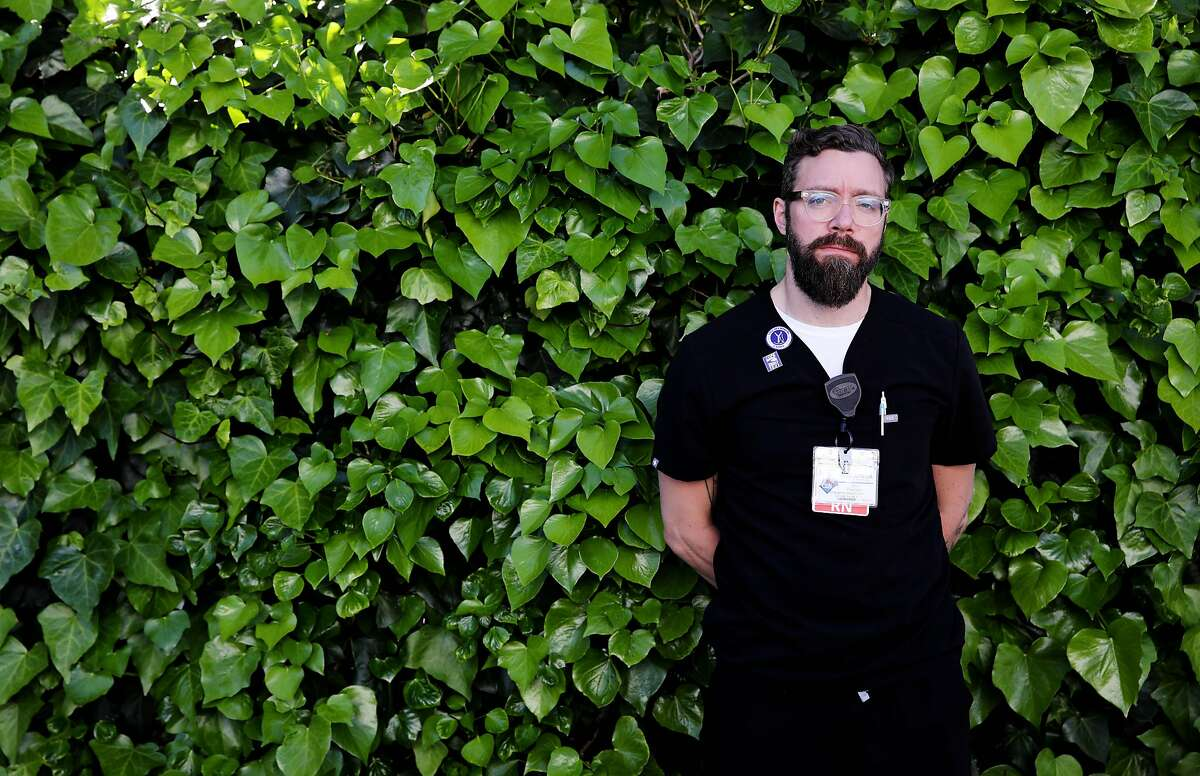 John Pearson, 40, an emergency department clinical nurse II, Alameda Health System, poses for a portrait on Wednesday, April 1, 2020, in Oakland, Calif.