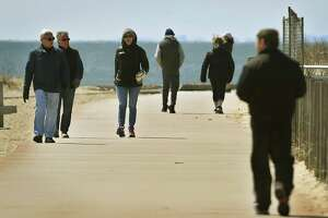 Visitors enjoy a sunny afternoon at Silver Sands State Park in Milford, Conn. on Wednesday, April 1, 2020. The Department of Energy and Environmental Protection announced plans to reduce capacity at popular parks to ensure social distancing in the wake of the coronavirus.