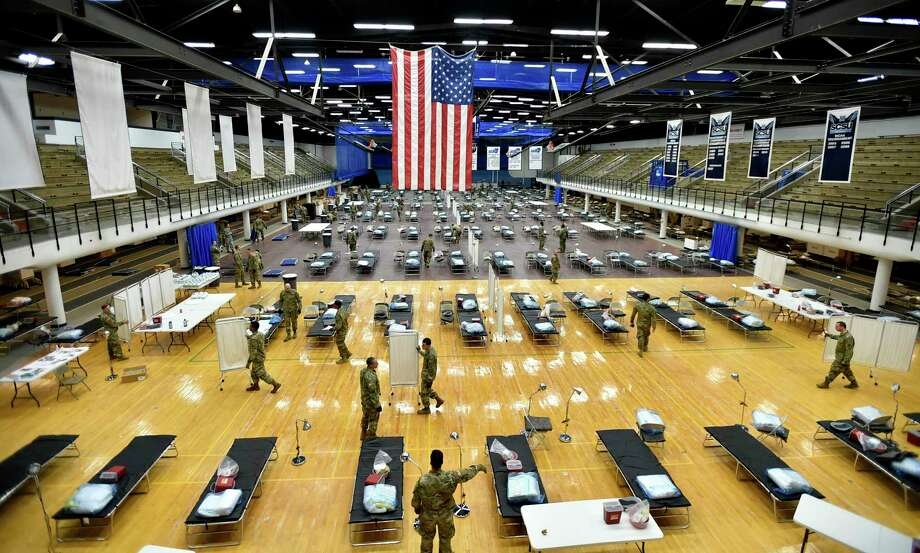 Seventy-five members of the Connecticut National Guard's 1-102nd Infantry stage a 250-bed medical station Wednesday in the Southern Connecticut State University Moore Field House in New Haven. Photo: Peter Hvizdak / Hearst Connecticut Media / New Haven Register