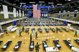 Seventy-five members of the Connecticut National Guard's 1-102nd Infantry stage a 250-bed medical station Wednesday in the Southern Connecticut State University Moore Field House in New Haven.