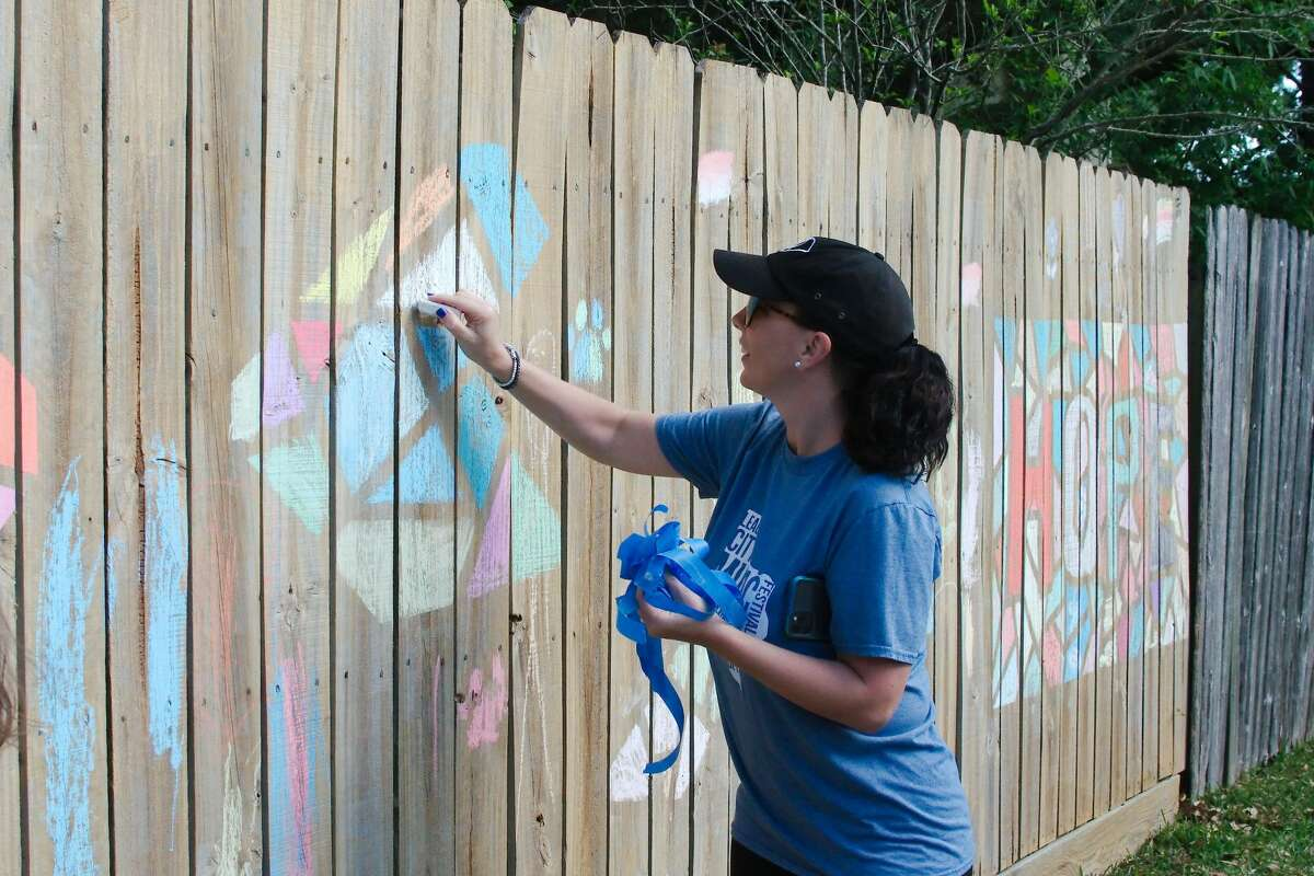 Samantha Thomas adds her touch to a chalk art mozaic as the League City residents create fence graffiti art in Brittany Bay to pass the time during the mandatory stay at home order to prevent the spread of COVID-19.
