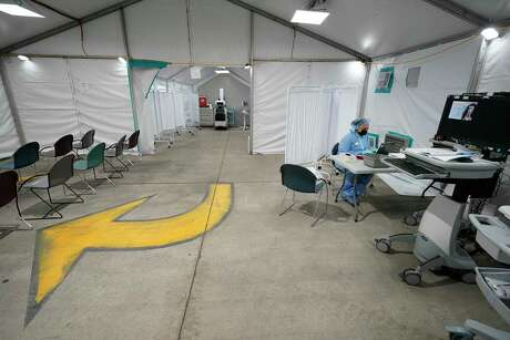 Dameka Larry, a patient access representative, works inside the Memorial Hermann Memorial City alternative care site tent for the care of potential COVID-19 patients Wednesday, April 1, 2020, in Houston. The hospital set up the tent inside the parking garage next to the emergency center.